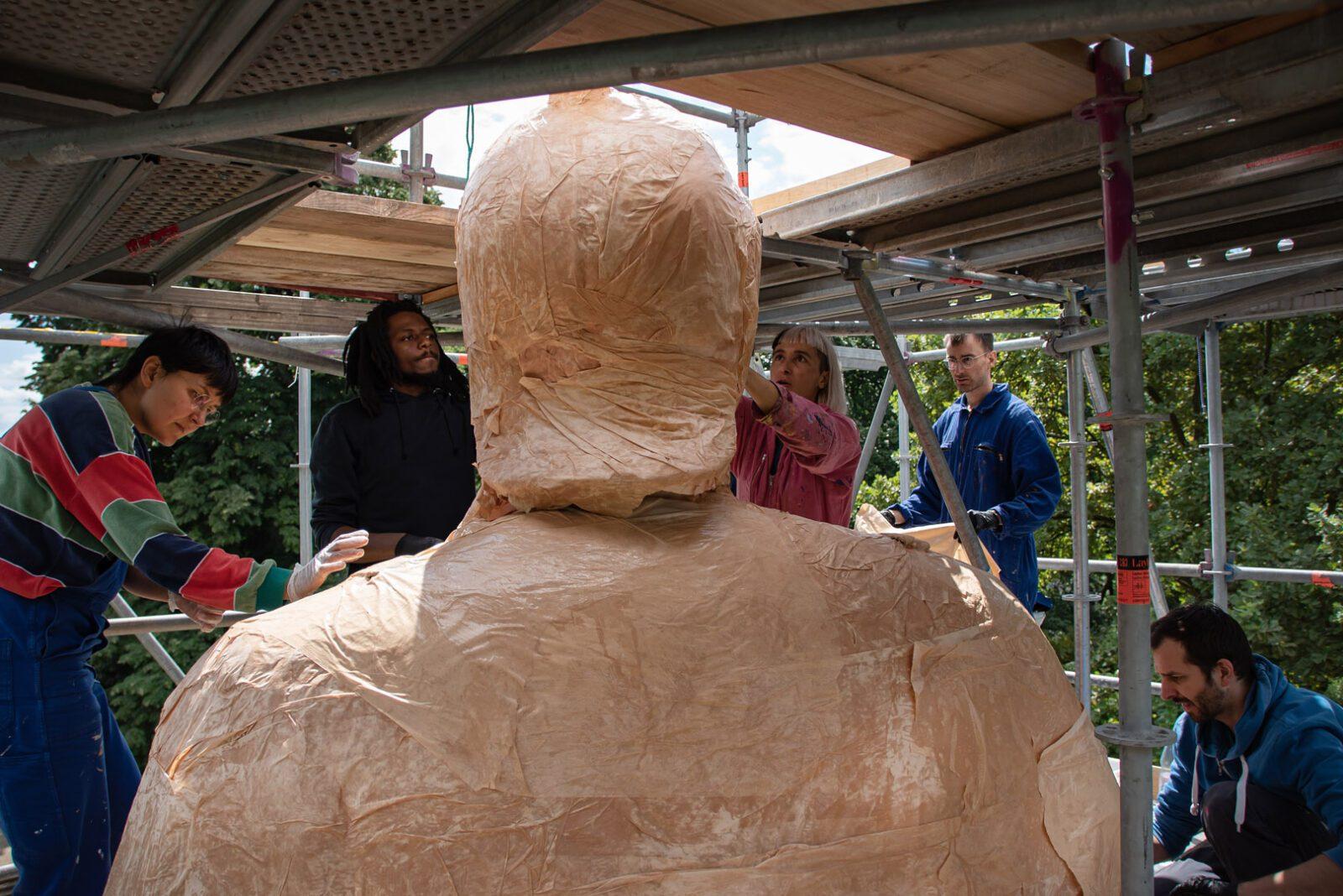 Kopf und Schultern der mit Papier verpackten Bismarck-Statue von hinten. Um die Figur herum 5 Menschen im Baugerüst bei der Arbeit.